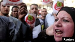 Egyptian protesters hold placards with the Arabic inscription reading 'danger' and shout slogans as they demonstrate against the International Monetary Fund (IMF) delegation visit, in front of the General-Prosecutor's office in Cairo Apr. 3, 2013.