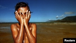 Seorang anak Aborigin bermain di dekat Cape Tribulation, Queensland. Setelah pergulatan hukum selama 30 tahun, kelompok-kelompok pribumi Semenanjung Cape York, Australia, merayakan dikembalikannya tanah kesukuan seluas lebih dari 160 ribu hektar.