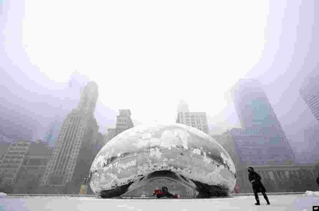 "A woman walks by the Cloud Gate Sculpture (known as ""The Bean"") during a snowstorm in Chicago, March 5, 2013."