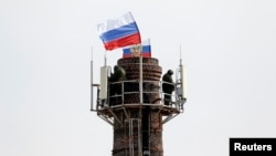 Orang-orang bersenjata yang diduga kuat bekerja untuk Rusia, berjaga di dekat cerobong asap dekat markas bear angkatan laut dan memasang bendera Rusia di Sevastopol (19/3).