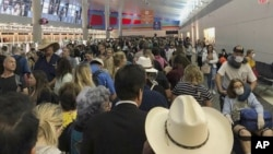 In this photo provided by Austin Boschen, people wait in line to go through the customs at Dallas Fort Worth International Airport in Grapevine, Texas, Saturday, March 14, 2020. International travelers reported long lines at the customs at the airport Sat