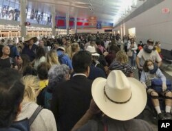In this photo provided by Austin Boschen, people wait in line to go through the customs at Dallas Fort Worth International Airport in Grapevine, Texas, Saturday, March 14, 2020. International travelers reported long lines at the customs at the airport.