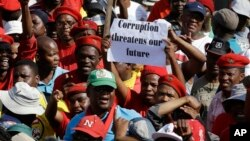 FILE - Protesters hold a placard demanding an end to corruption, at a rally in Pretoria, South Africa, Sept. 30, 2015.