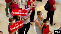 在觀塘一個商場觀看奧運電視直播的市民手持標語,支持香港單車選手李慧詩。(美國之音/湯惠芸)