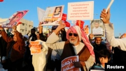 """FILE - An anti-government protester holds a sign reading """"It Is Impossible For The Bahraini People To Give up On Democracy"""" as he shouts anti-government slogans during a rally in the village of Bilad al-Qadeem south of Manama, Feb. 11, 2014."""
