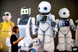Seorang pengunjung berjalan melewati mural yang menampilkan robot dari pembuat robot China Canbot di Konferensi Robot Dunia di Beijing, Cina, Rabu, 15 Agustus 2018. (Foto: AP)