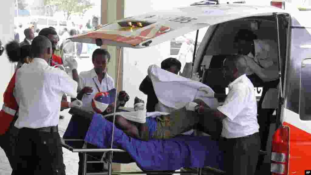 Un blessé, entouré des médecins et du personnel soignant, est transporté sur un civière après qu'une ambulance l'a amené à l'Hôpital national Kenyatta de Nairobi, au Kenya, Mardi 7 Juillet 2015