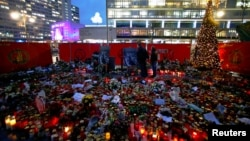 Flowers and candles are placed at the former Christmas market in Berlin, Germany, Jan. 3, 2017, following an attack by a truck in December which plowed through a crowd at the market.