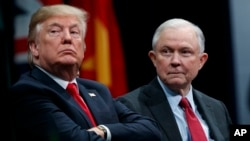 FILE - President Donald Trump sits with Attorney General Jeff Sessions during the FBI National Academy graduation ceremony in Quantico, Va.