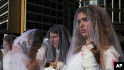 Para perempuan Lebanon mengenakan baju pengantin yang dibubuhi pewarna merah darah dalam unjuk rasa memprotes peraturan yang membebaskan pemerkosa jika menikahi korbannya, di Beirut, Lebanon, 6 Desember 16.