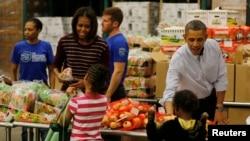 Presiden AS Barack Obama dan ibu negara Michelle Obama menyerahkan bantuan makanan untuk Thanksgiving kepada warga kurang mampu di Washington DC (27/11).