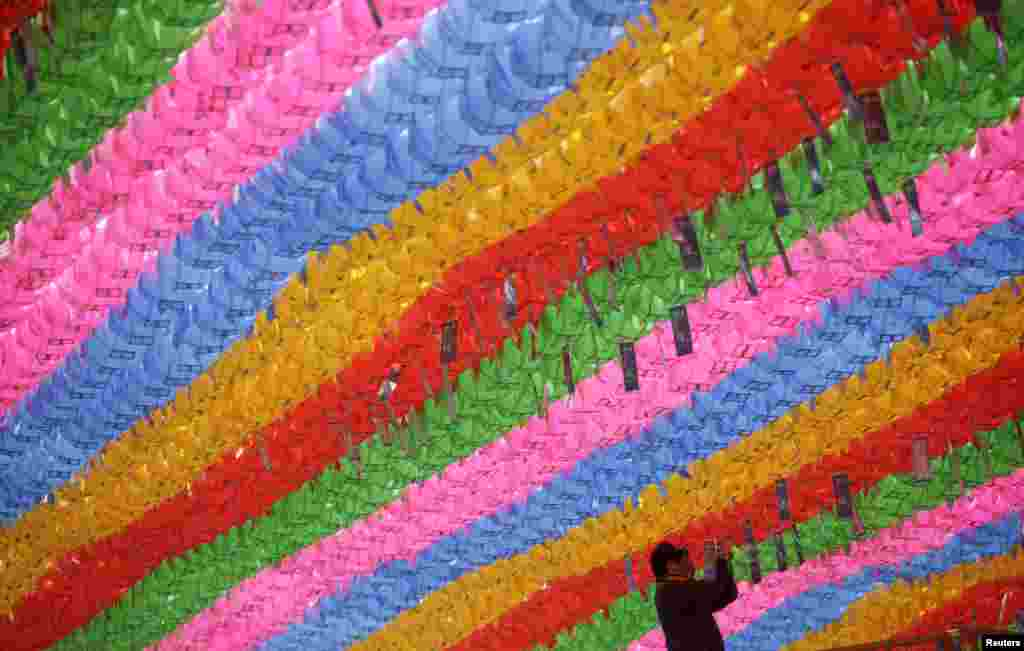 A worker attaches prayer petitions, with names written on cards, to lotus lanterns in preparation for the upcoming birthday of Buddha at Jogye temple in Seoul. Buddha's birthday falls on May 6 in South Korea.