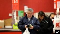 Seorang pria memeriksa uang kembalian setelah berbelanja di toko Kmart di New York. (Foto: Dok)