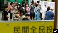 홍콩 주민들이 22일, 홍콩 곳곳에 문을 연 투표소에서 행정장관 선출 방식 개혁을 위한 비공식 주민 투표에 참여하고 있다.
