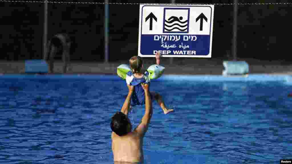 Hai cha con người Israel trong hồ bơi tại Kibbutz Yad Mordechai, gần biên giới phía bắc dải Gaza, ngày 6/8/2014.