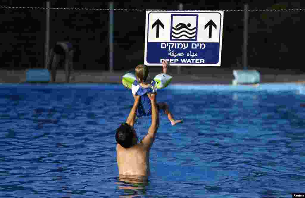 An Israeli man holds his son in the pool at Kibbutz Yad Mordechai, near the border with northern Gaza, Aug. 6, 2014.