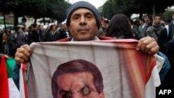 Một người biểu tình cầm bức hình bị đốt của cựu Tổng thống Ben Ali trong một cuộc biểu tình đòi loại trừ các viên chức của chế độ đã bị lật đổ vẫn còn trong chính phủ