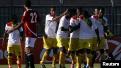 FILE - Guinea's players celebrate scoring a goal against Egypt during their 2014 World Cup qualifying soccer match in Hurghada, Egypt, Sep. 10, 2013.