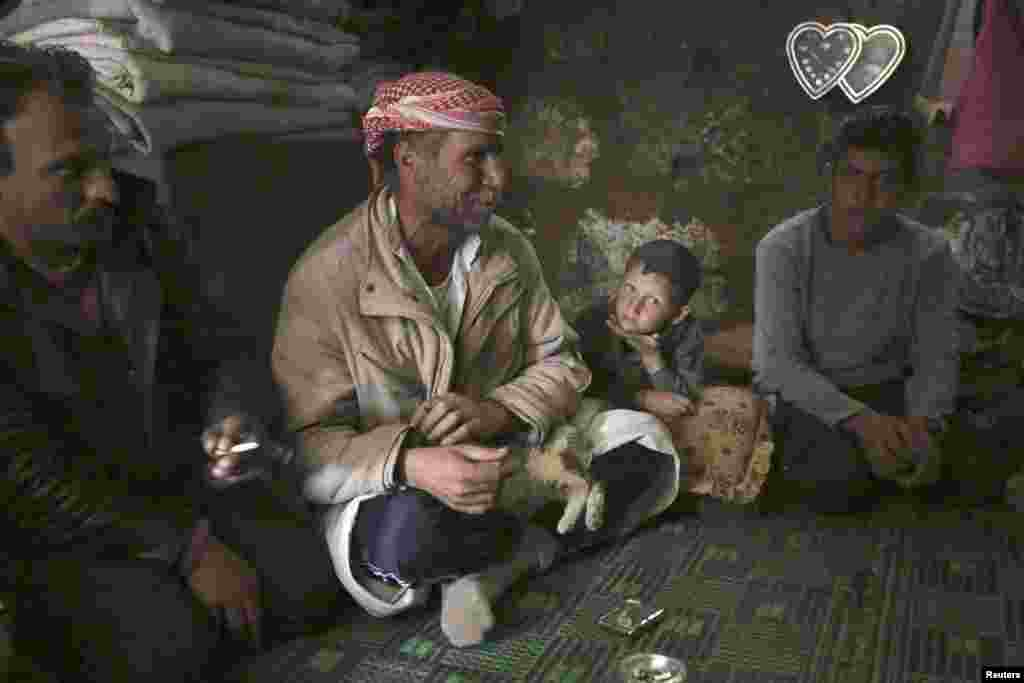 A refugee family from Kvromh village sit inside a makeshift house in the Serjilla archaeological site of Jabal al-Zawiya, Syria, March 29, 2014.