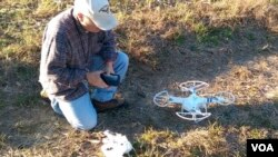 Don Hervig ties a meat lure to a quad-copter, to train his Apolmado falcon. (M. Osborne/VOA)