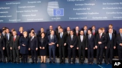 Heads of State and government pose for a group photo at an EU summit in Brussels, Feb. 12, 2015.