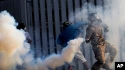 反政府抗议者在曼谷一座体育场与防暴警察冲突。图为抗议者把警察发射的催泪瓦斯罐投掷回去。