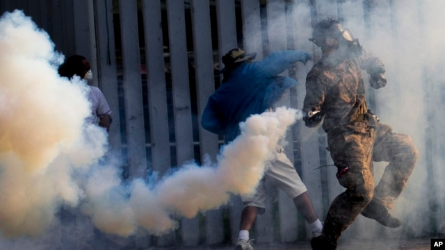 Anti-government protesters throw back tear gas canisters to riot policemen during a clash at a sport stadium in Bangkok, Thailand, Dec. 26, 2013.