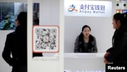 FILE - A sales assistant sits behind and under Alipay logos at a train station in Shanghai, Feb. 9, 2015. Apple Pay has joined China's fast-growing mobile payment market and is challenging two major local brands, Alipay and WeChat Wallet.