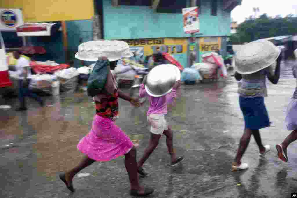 Women cover their heads with pans as they walk in a light rain brought by Hurricane Matthew in Port-au-Prince, Haiti, Oct. 4, 2016. Hurricane Matthew roared into the southwestern coast of Haiti, threatening a largely rural corner of the impoverished country with devastating storm conditions as it headed north toward Cuba and the eastern coast of Florida.