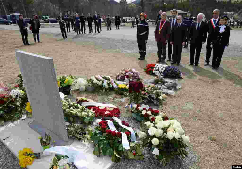 French Interior Minister Bernard Cazeneuve (C), Le Vernet Mayor Francois Balique (5thR), Prefect of the Alpes de Haute-Provence region, Patricia Willaert (R) and President of the Var departmental council, Michel Vauzelle (3rdR), spend a moment of silence after laying a wreath in memory of the victims of the Germanwings Airbus A320 crash, in the village of Le Vernet, French Alps.
