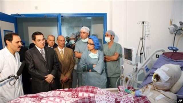 In this photo released 28 Dec 2010 by the Tunisian President's office, Tunisia's President Zine El Abidine Ben Ali, second from left, visits Mohamed Bouazizi, a young man who set himself on fire after police confiscated fruit and vegetables he sold withou