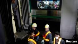 首尔一地铁站内工人在检查事故,对面车厢内乘客正在观望。2014年5月2日拍摄