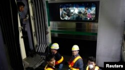 Para penumpang dari arah yang berlawanan, mengamati kerusakan pada kereta api bawah tanah (subway) saat para pekerja tengah memeriksanya pasca tabrakan di dekat stasiun Sangwangsimni, sebelah timur kota Seoul, Korea Selatan (2/5).