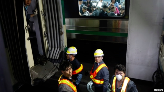 Passengers on the opposite side look at a damaged subway train as workers check it at a subway station in Seoul, May 2, 2014.