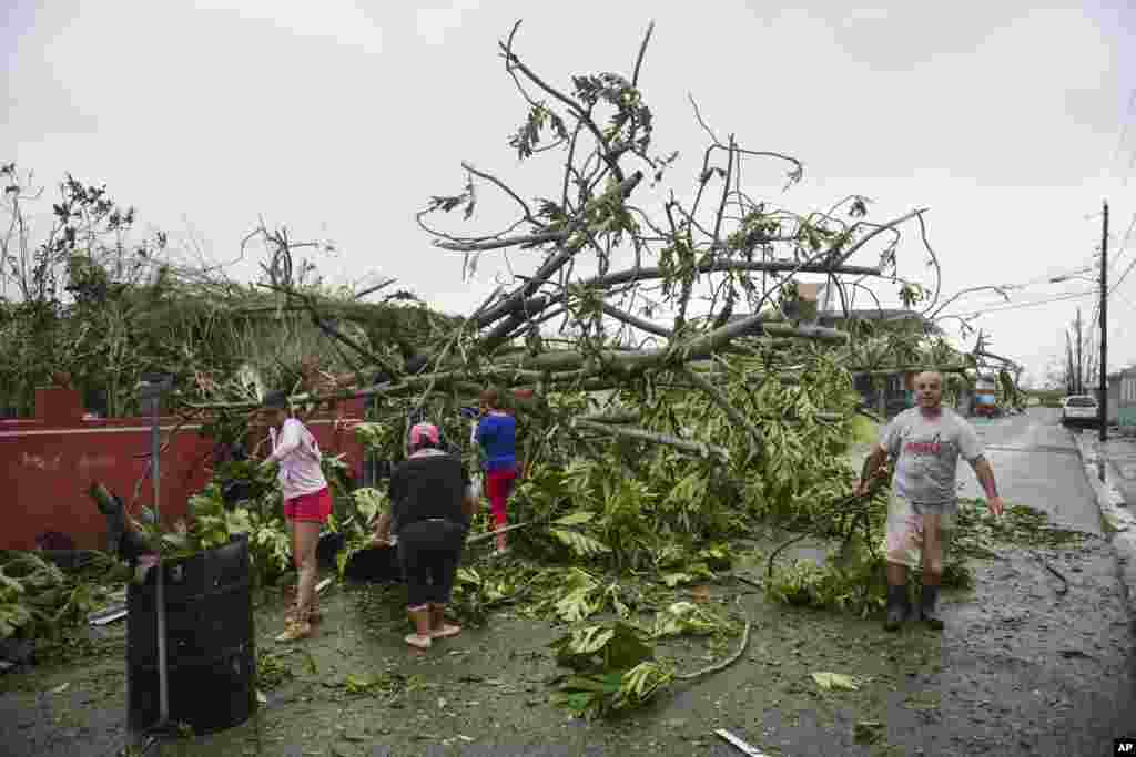 A family helps clean the road after Hurricane Maria hit the eastern region of the island, in Humacao, Puerto Rico, Sept. 20, 2017.