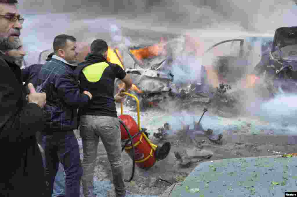 Civil Defense members move a fire extinguisher as a Hezbollah member carries a walkie-talkie at the site of an explosion in Haret Hreik, Beirut, Jan. 21, 2014.