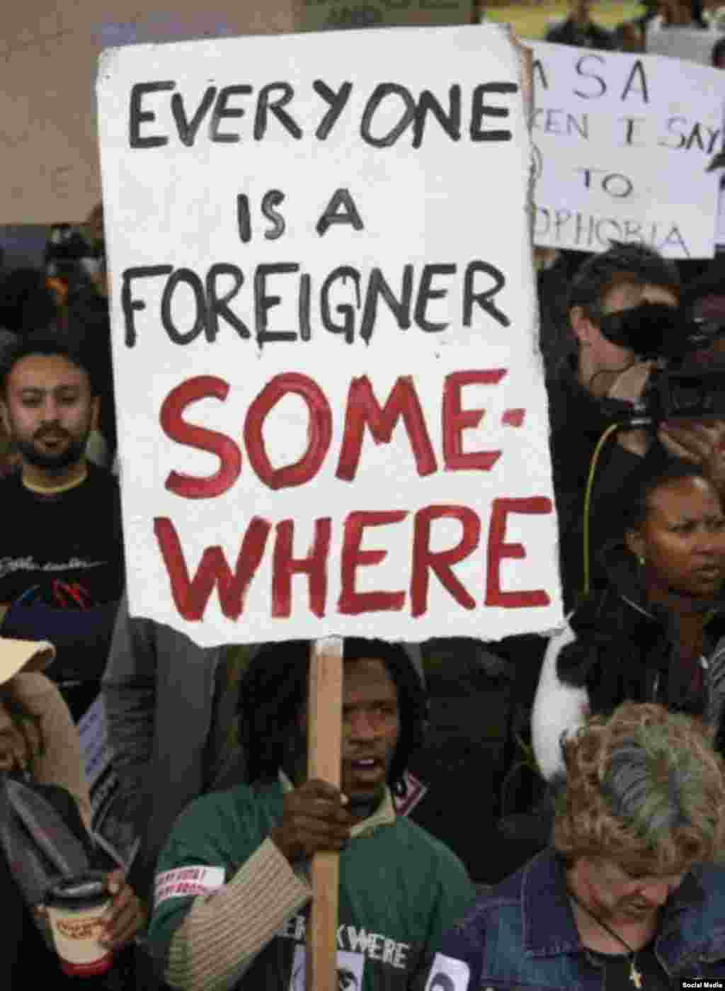 """Grupo protesta a violência com uma placa que diz """"Somos todos imigrantes em algum lugar"""""""
