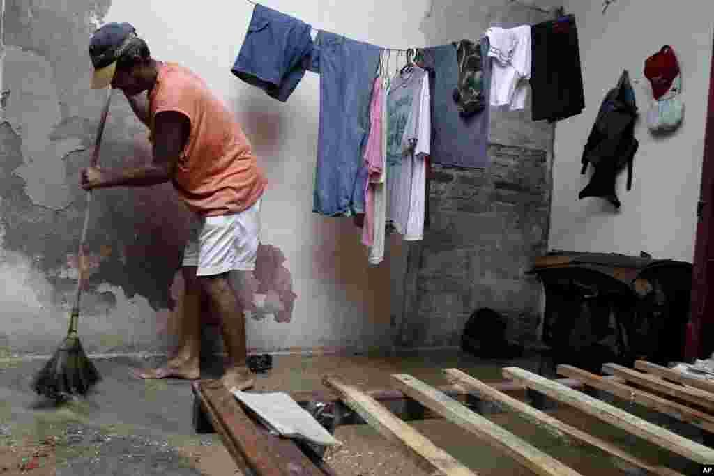 کیوبا میں طوفان گذرنے کے بعد ایک شخص اپنے گھر کی صفائی کررہاہے