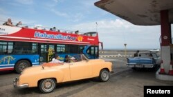 """FILE - A vintage car carrying tourists waits in line to fill up with fuel at a gas station as a tourist bus passes by along the seafront boulevard """"El Malecon"""" in Havana, January 12, 2015."""