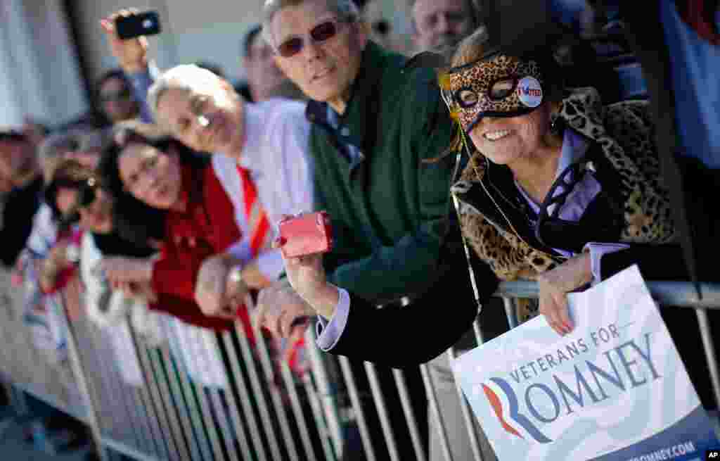 Wearing a mask on Halloween, Carol Heye of Riverview, Florida, shows her support for Mitt Romney as he campaigns in Tampa, Florida.