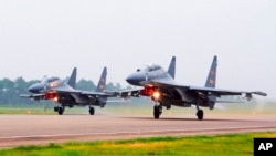 FILE - Two Chinese SU-30 fighter jets take off from an unspecified location to fly a patrol over the South China Sea, in this undated file photo released by China's Xinhua News Agency.