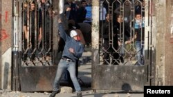 Seorang mahasiswa Universitas Al-Azhar University pendukung mantan Presiden Morsi melempar batu ke arah pasukan keamanan Mesir di distril Nasr City, Kairo (8/1).