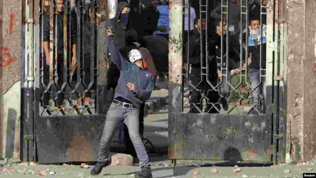 A student of Al-Azhar University, who is a supporter of the Muslim Brotherhood and deposed Egyptian President Mohamed Morsi, throws a stone during clashes with police in Cairo's Nasr City district, Jan. 8, 2014.