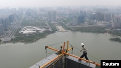 FILE - A worker walks on the roof of an office building construction site near a lake in Hefei, Anhui province.