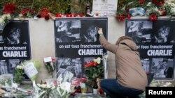 មនុស្សម្នាក់បានដាក់ផ្កានៅខាងមុខការិយាល័យកាសែត Paris Weekly 'Charlie Hebdo' នៅថ្ងៃទី០៨ ខែមករា ឆ្នាំ២០១៥។