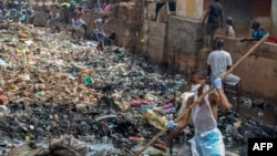 """FILE - Residents of Freetown take part in """"National Cleaning Day"""" on May 5, 2018. The first Saturday of each month, citizens of Sierra Leone are called to clean their streets."""