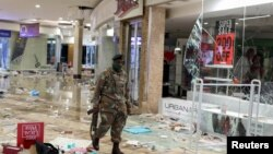 A member of the military walks as he inspects the damage at the looted Jabulani mall as the country deploys army to quell unrest linked to jailing of former President Jacob Zuma, in Soweto, South Africa, July 13, 2021.