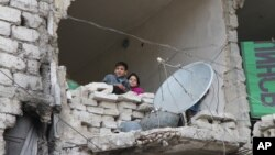 Niños se refugian en casas parcialmente destruidas en Alepo, Siria, mientras continúan los bombardeos.