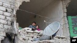 Des enfants dans une maison détruite pendant la guerre, à Alep en Syrie, le 11 février 2016.