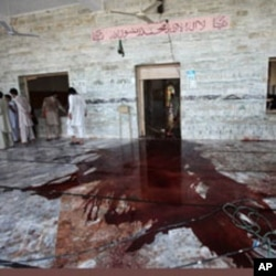 A Pakistani villager sweeps the floor of a mosque targeted by a suicide bomber in Khyber, Aug. 19, 2011.